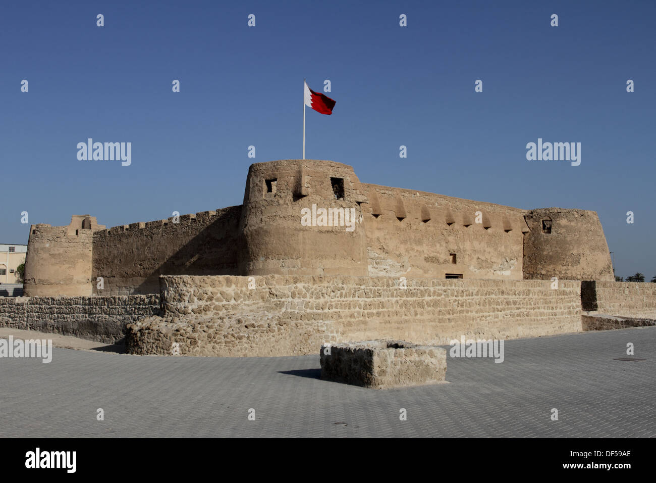 Arad Fort in Muharraq, Kingdom of Bahrain, with the Bahrain flag flying - Stock Image