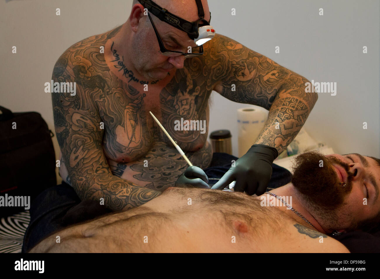 A tattooist creating new tattoo using traditional hand tapping during the Tattoo Convention 2013 in Katowice, Poland. - Stock Image