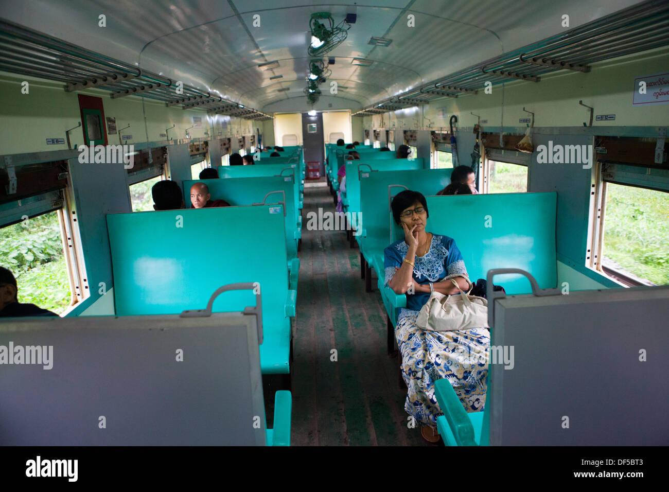 People ride in a railroad car in Yangon, Burma. - Stock Image