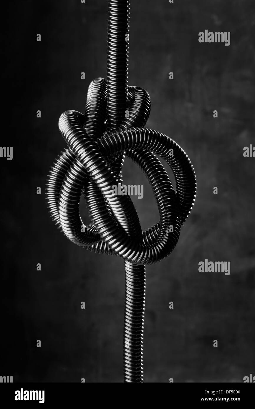 Black and white image of a black tangled flexible hose. - Stock Image