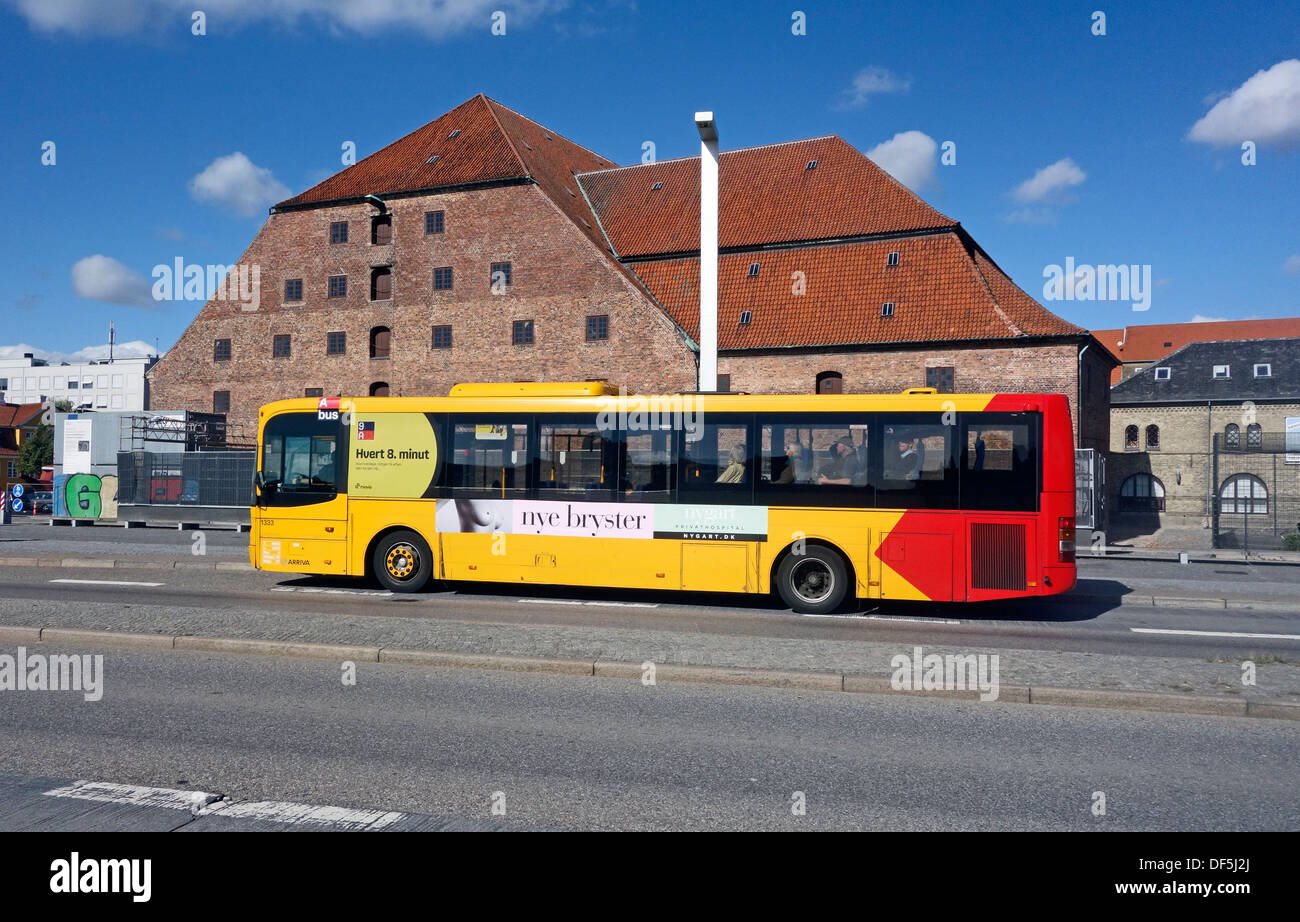 A Bus 9A passing along Christians Brygge on Slotsholmen in central Copenhagen Denmark displaying an advert for 'nye bryster' - Stock Image