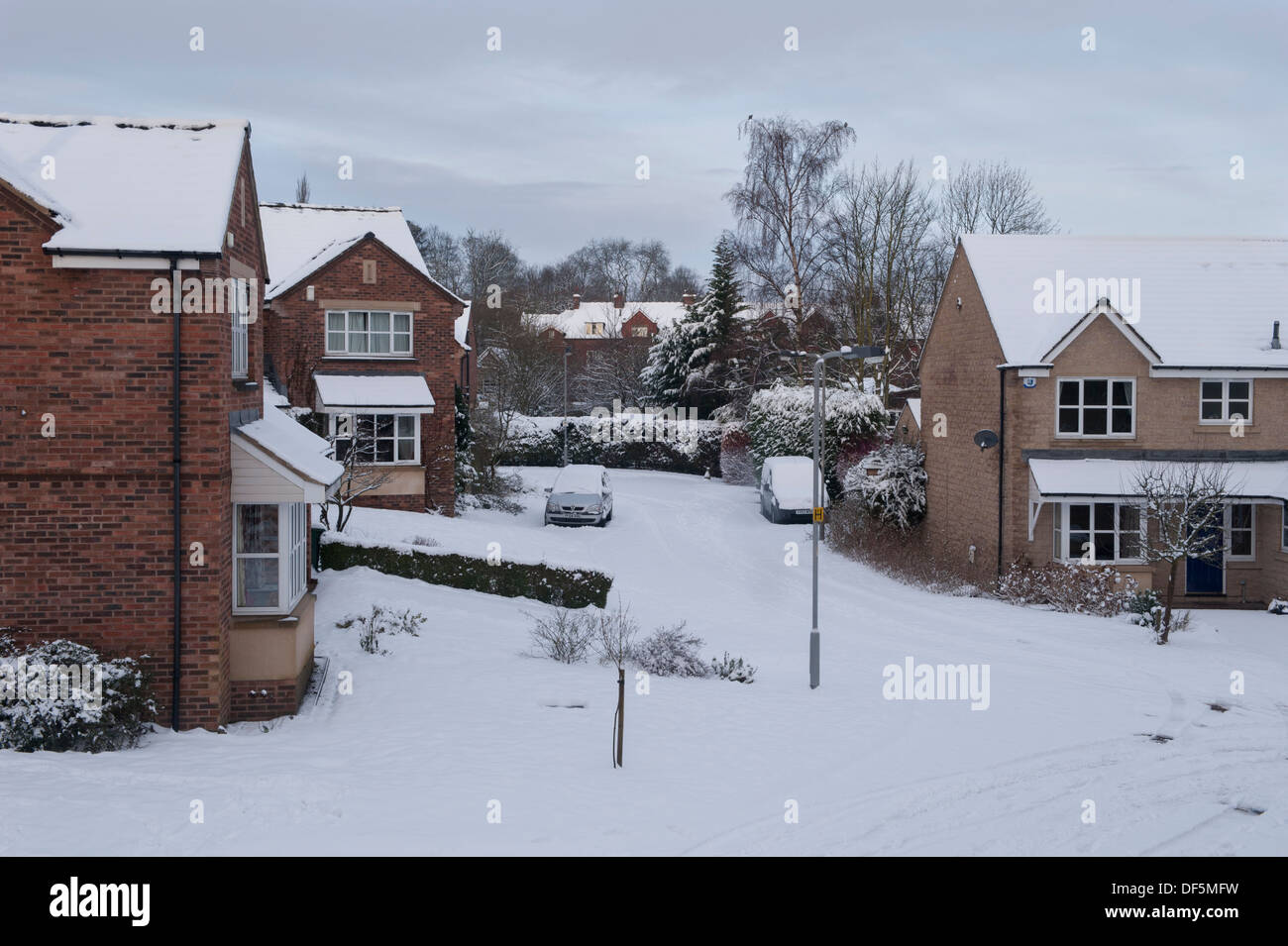 High view over residential area with modern detached houses in a quiet, snow-covered cul-de-sac on cold winter day Stock Photo