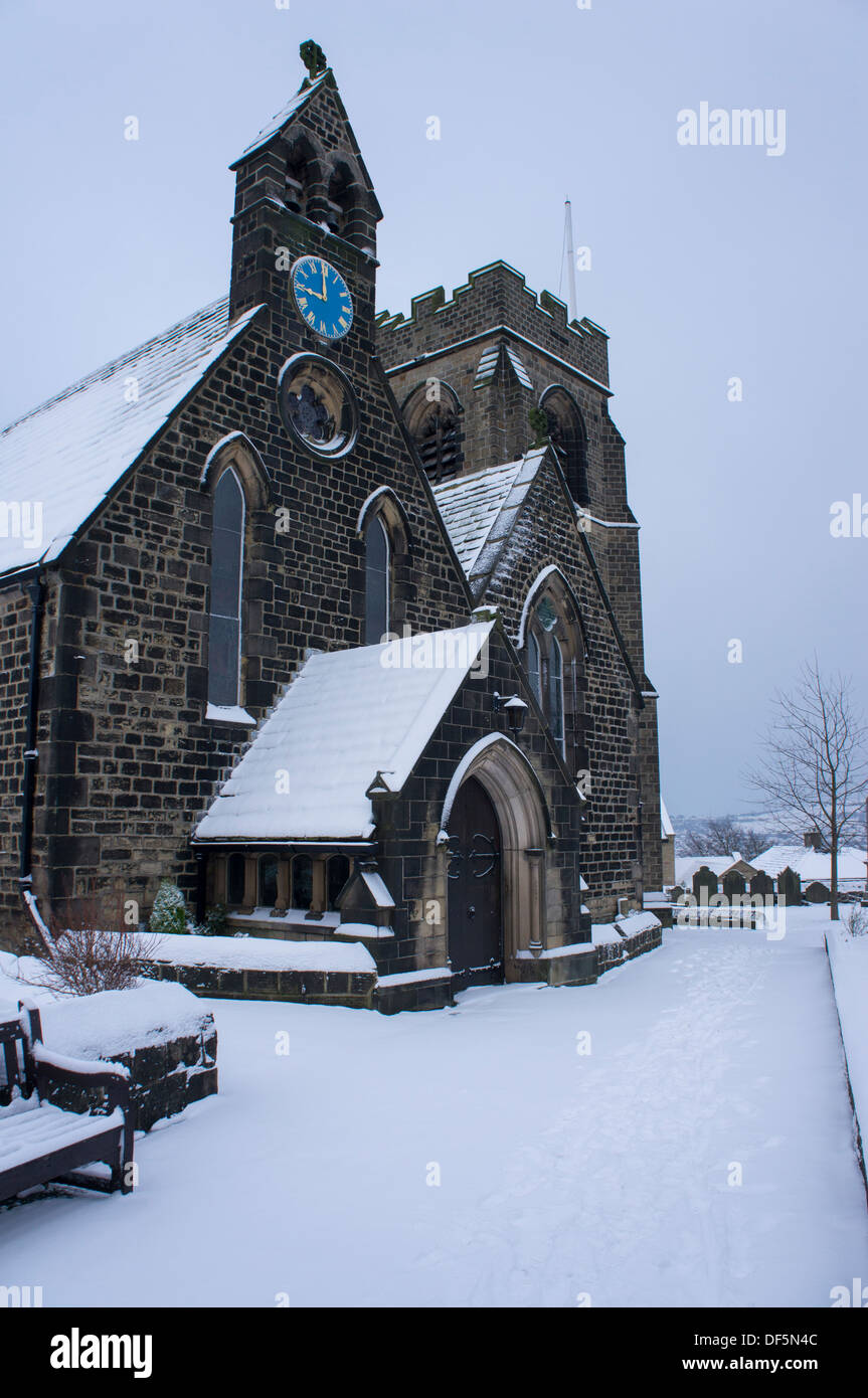 Cold, grey winter scene with snow falling on St. John's Church (building & path covered with white layer) - Stock Image