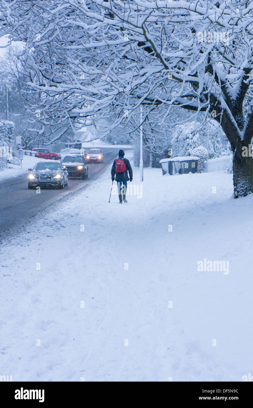 Winter scene with snowy driving conditions for cars on road & lone pedestrian walking on snow-covered pavement  Stock Photo