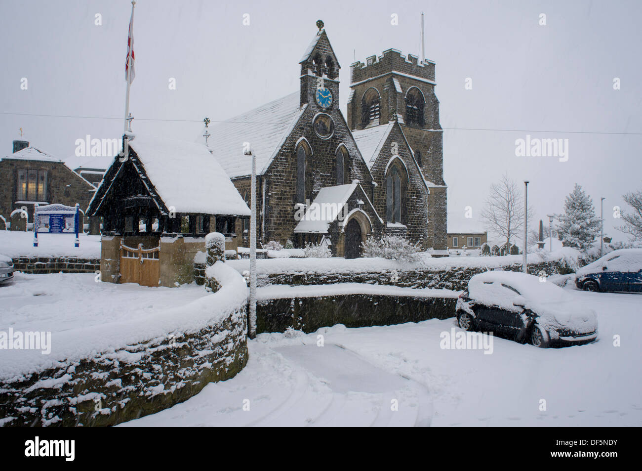 Cold, grey winter scene with snow falling on St. John's Church (buildings & cars covered with white layer) - Baildon, West Yorkshire, England, UK. - Stock Image