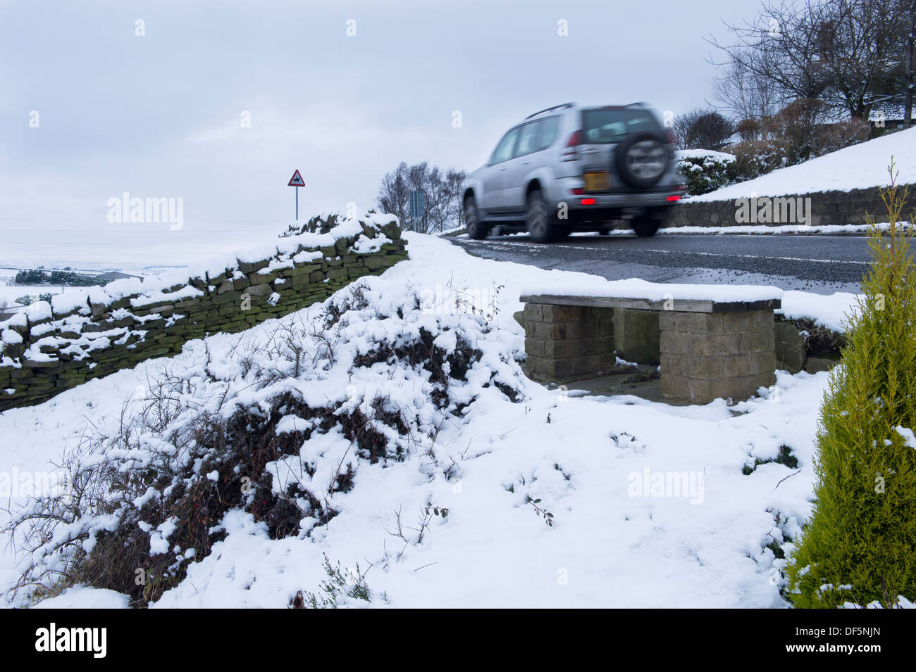 Blurred motion of Toyota Land Cruiser 4x4, traveling past white fields along country lane on a cold, snowy winter's day - West Yorkshire, England, UK. - Stock Image