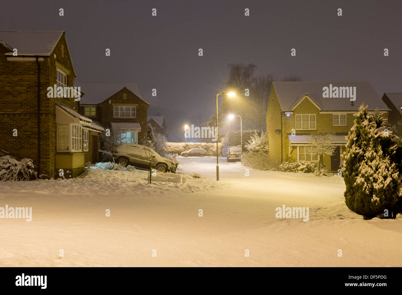 Starburst light from steet lamps at nighttime illuminate private modern houses in cold, snow covered cul-de-sac Stock Photo