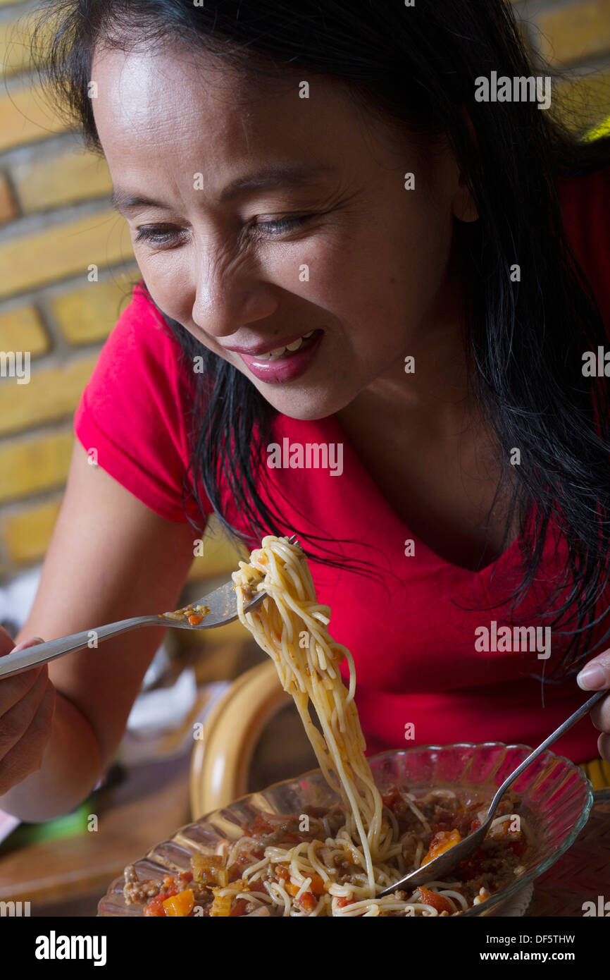 Asian Woman Eating Pasta Noodles on Fork - Stock Image