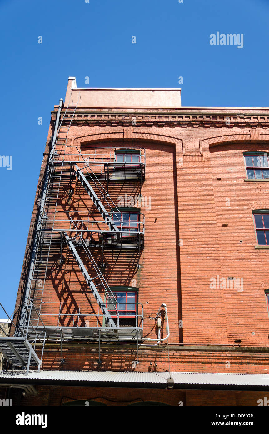 Fire escape running down the side of a red brick building in Portland, Oregon - Stock Image