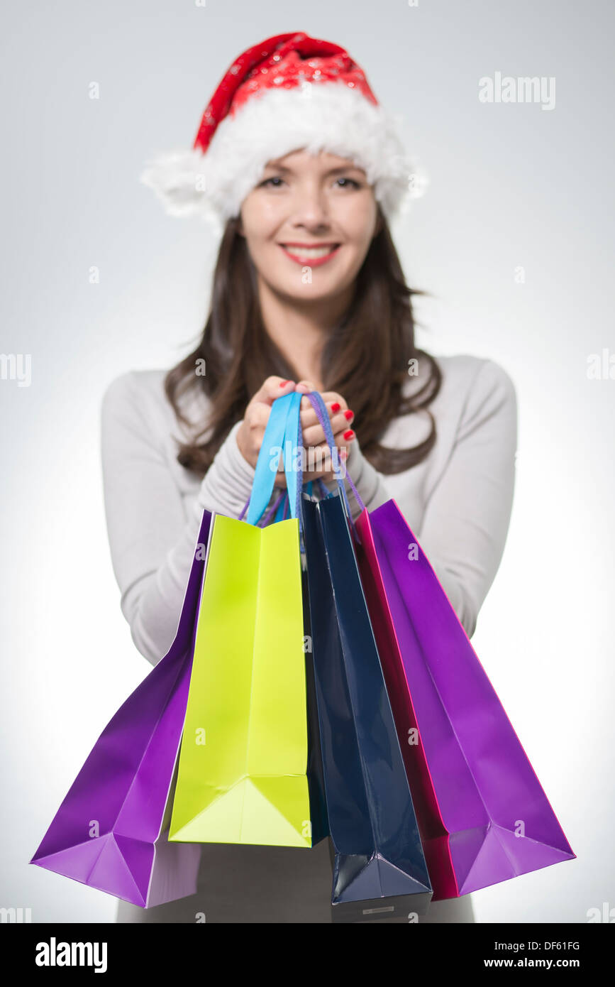 12401a4dc7520 beautiful brunette woman with red santa hat holding colorful shopping bags  from Christmas shopping