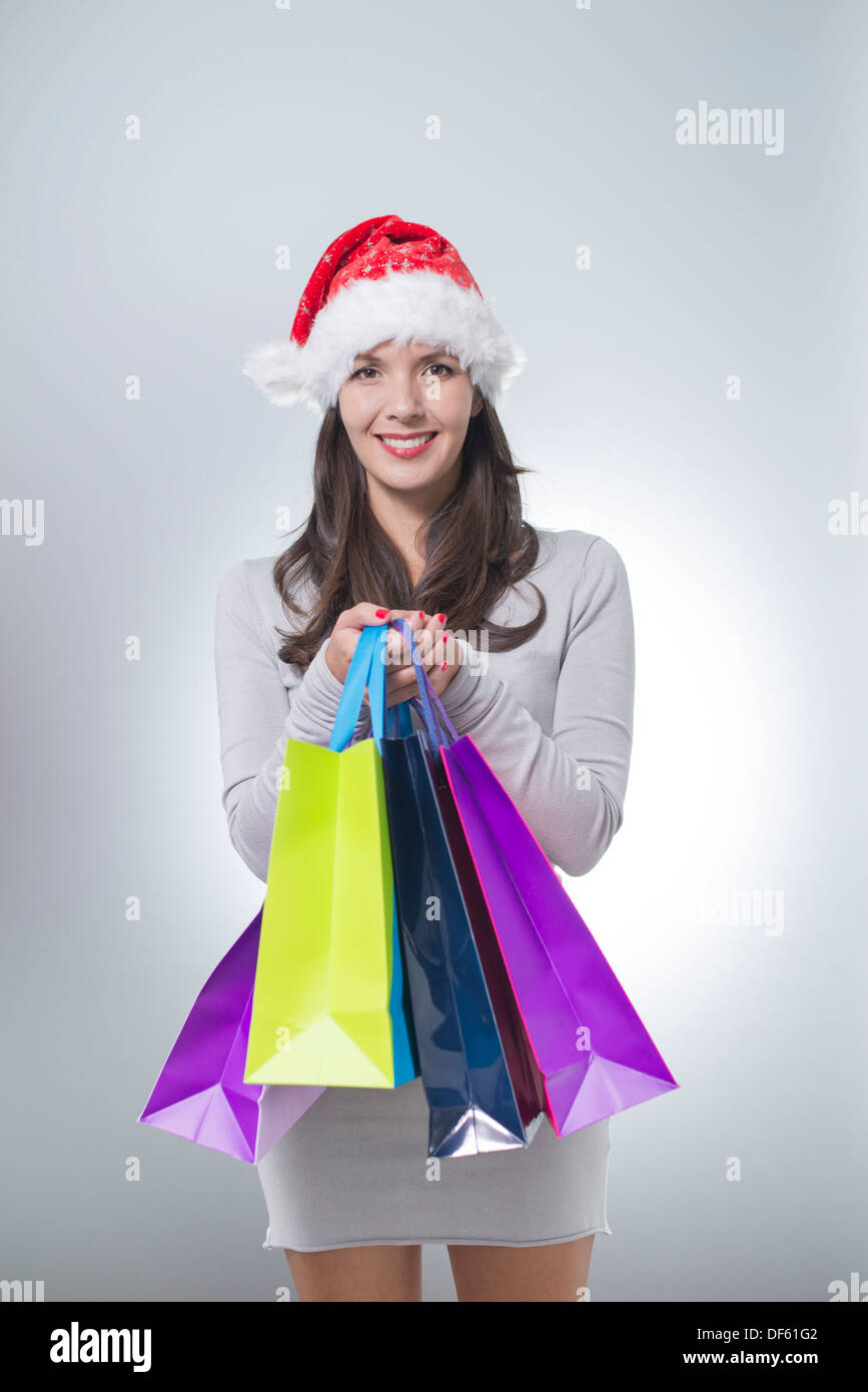 f0d48a98fbb1e beautiful brunette woman with red santa hat holding colorful shopping bags  from Christmas shopping - Stock