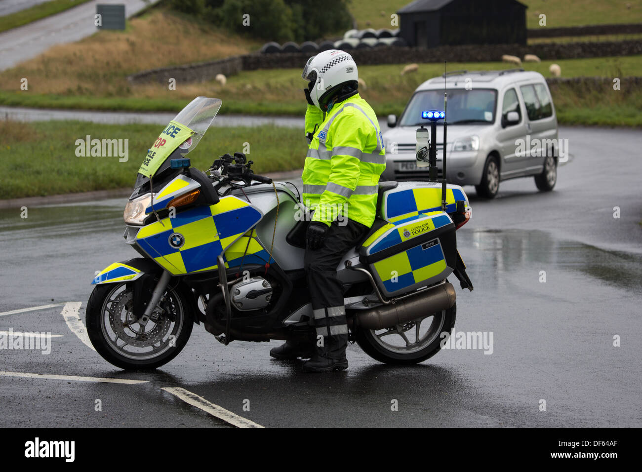 A Motorcycle Police Traffic Officer directing traffic at a road block - Stock Image