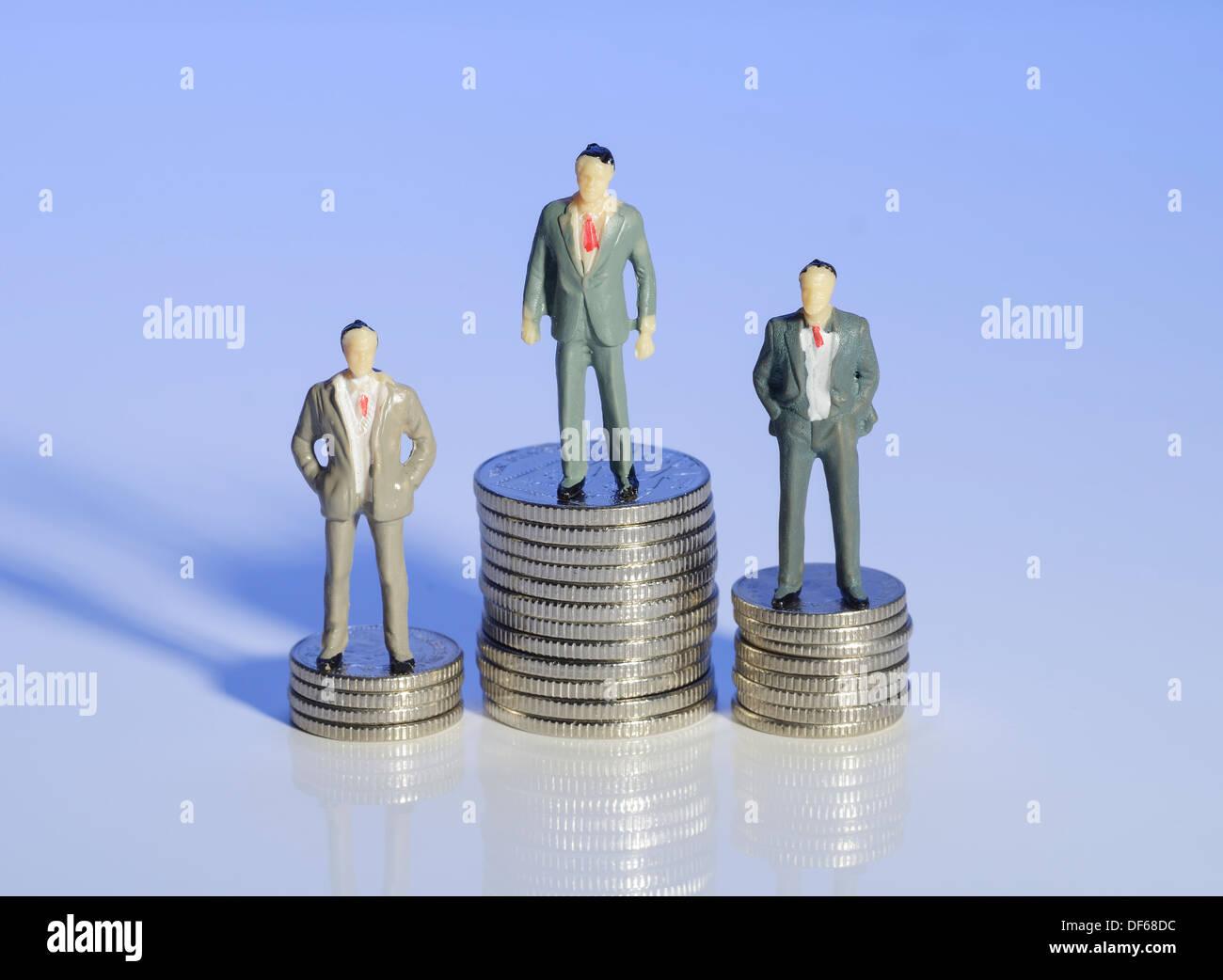 Mini plastic business men standing on piles of money - Stock Image