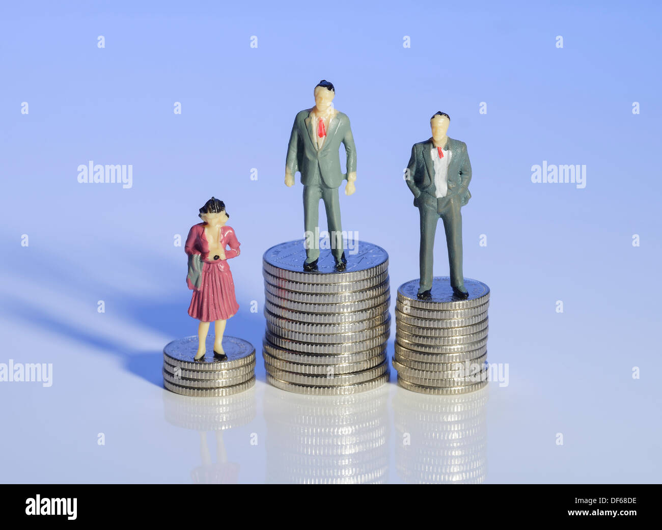 Mini plastic men and a woman standing on piles of money - Stock Image