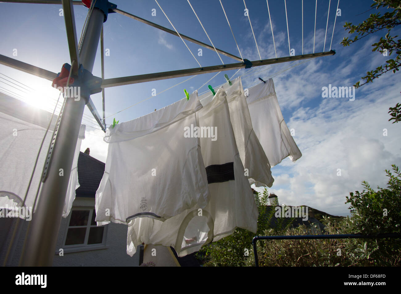 White tee-shirts hanging on a rotary drier, in a garden, blue sky and white clouds in the background - Stock Image