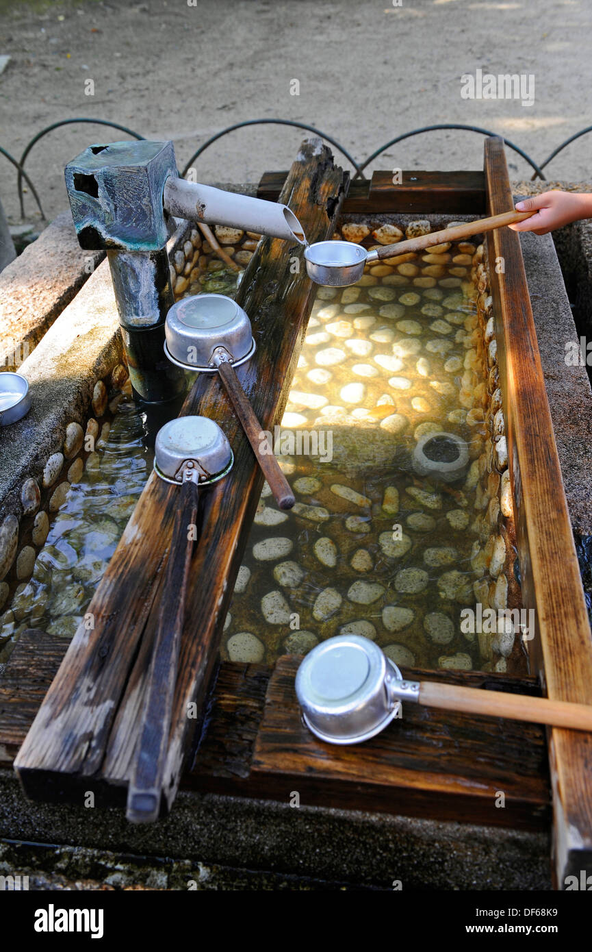 Long handled drinking and washing metal cups with fresh water. - Stock Image