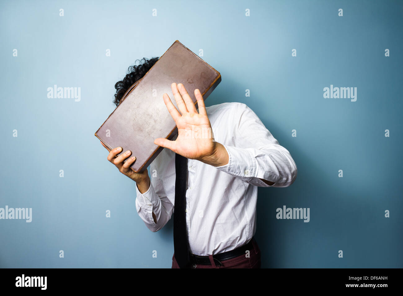 Young man doesn't want his photo taken and is hiding his face behind a briefcase - Stock Image
