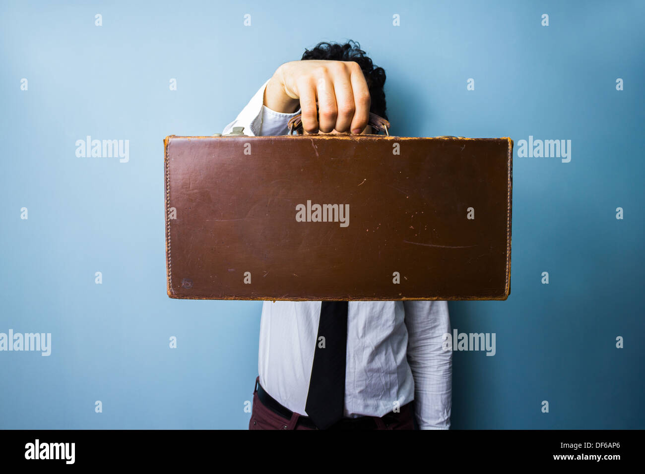 Young businessman holding an old briefcase in front of his face - Stock Image