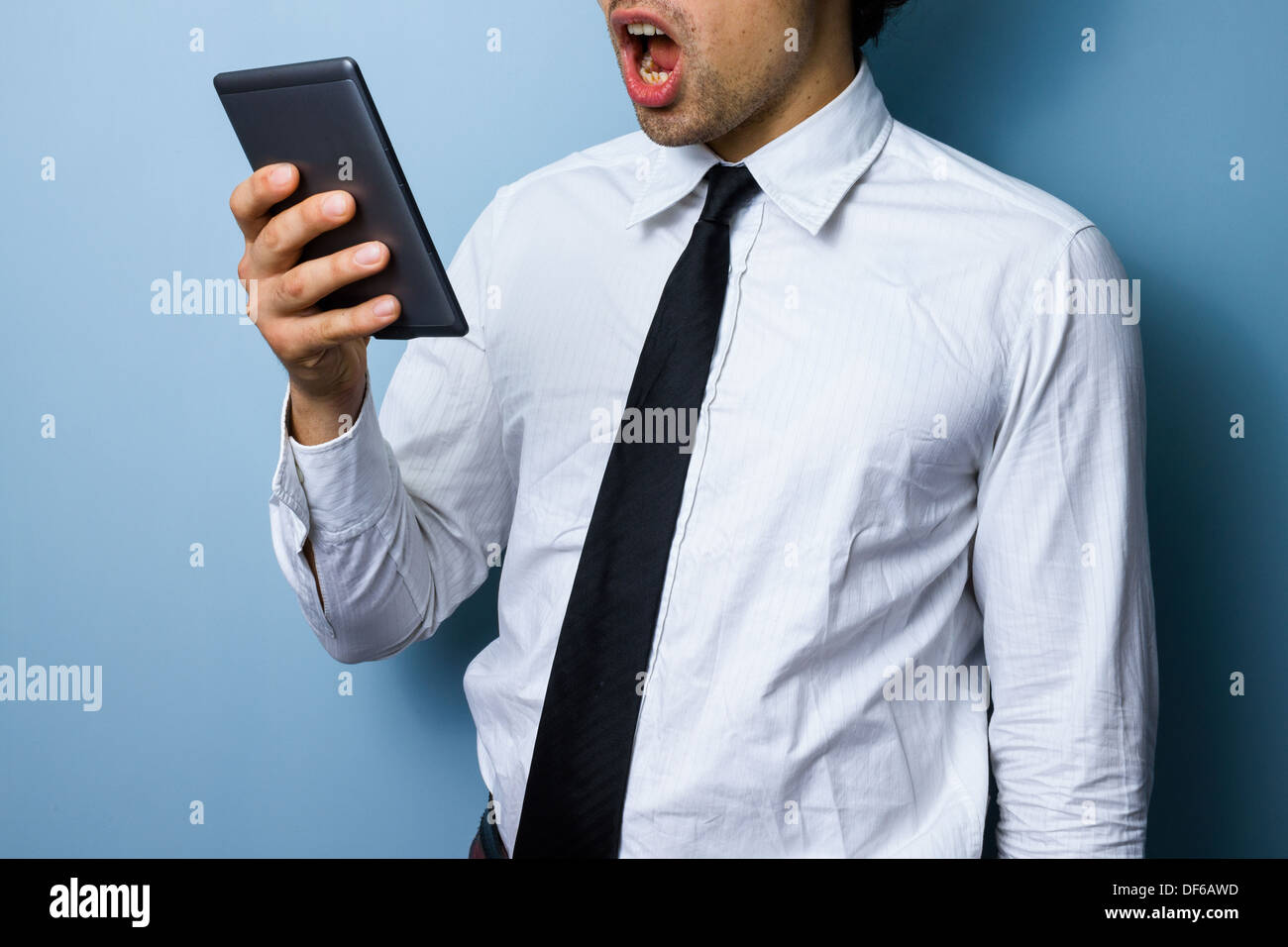 Young businessman is surprised by what he is reading on his digital tablet - Stock Image