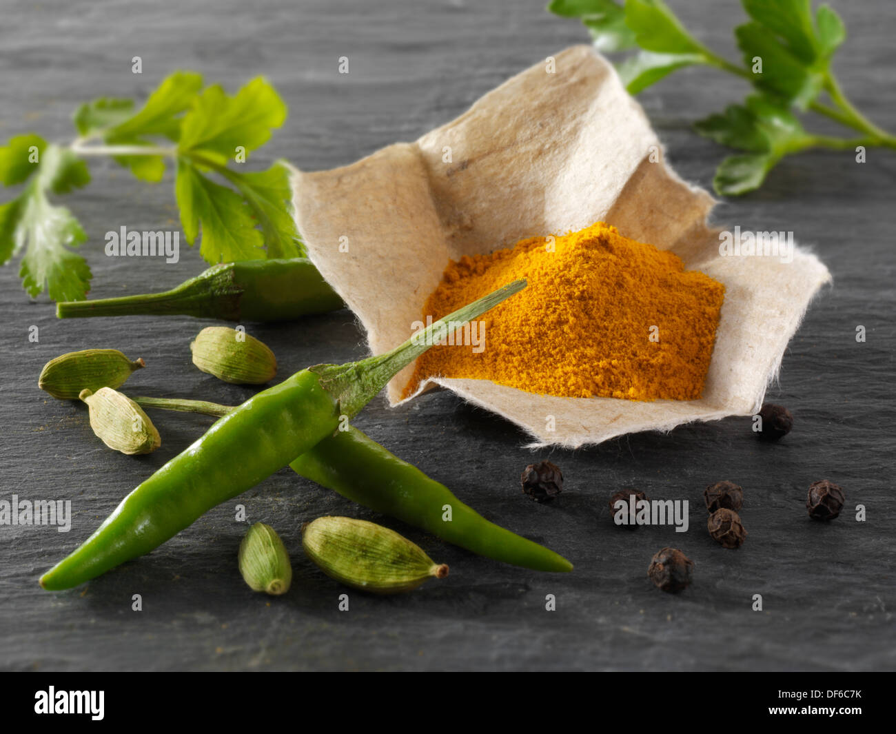 Fresh green birdseye chillies with ground turmeric & coriander leaves Indian spices composed arrangement - Stock Image