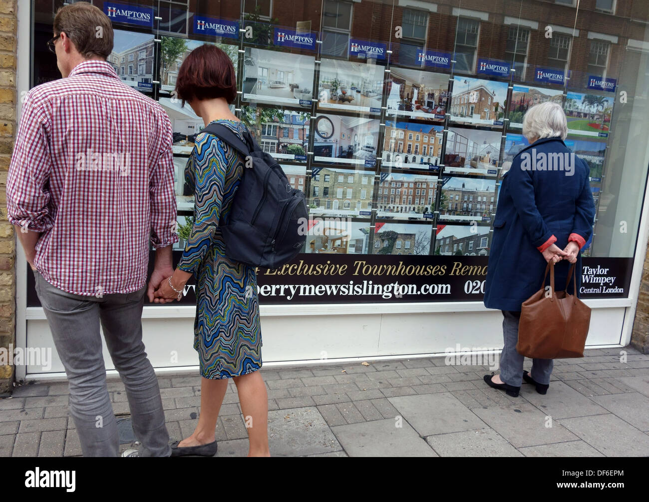 People looking at estate agents window display, London - Stock Image
