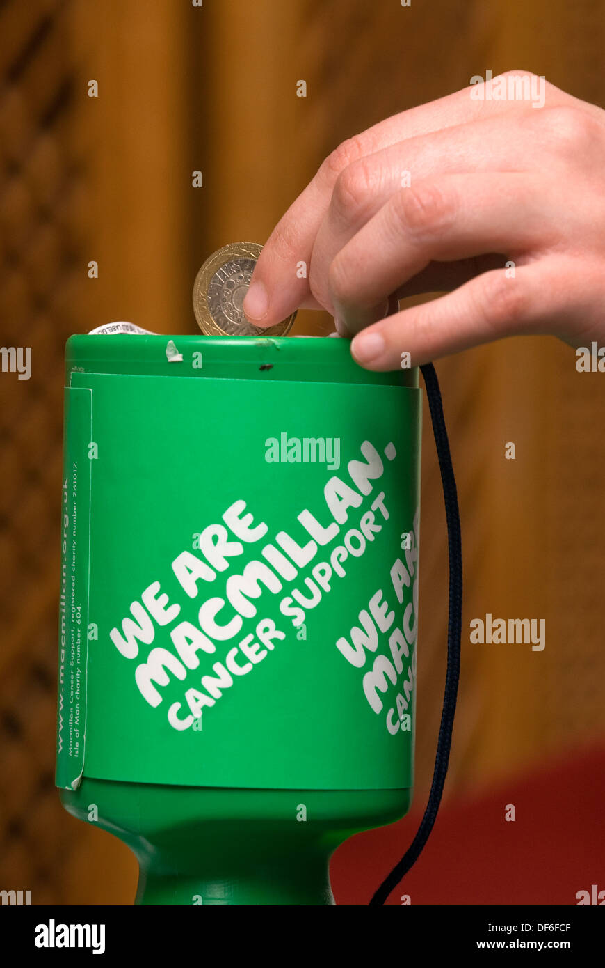 Making a £2 donation to Macmillan Cancer Support, Surrey, UK. - Stock Image