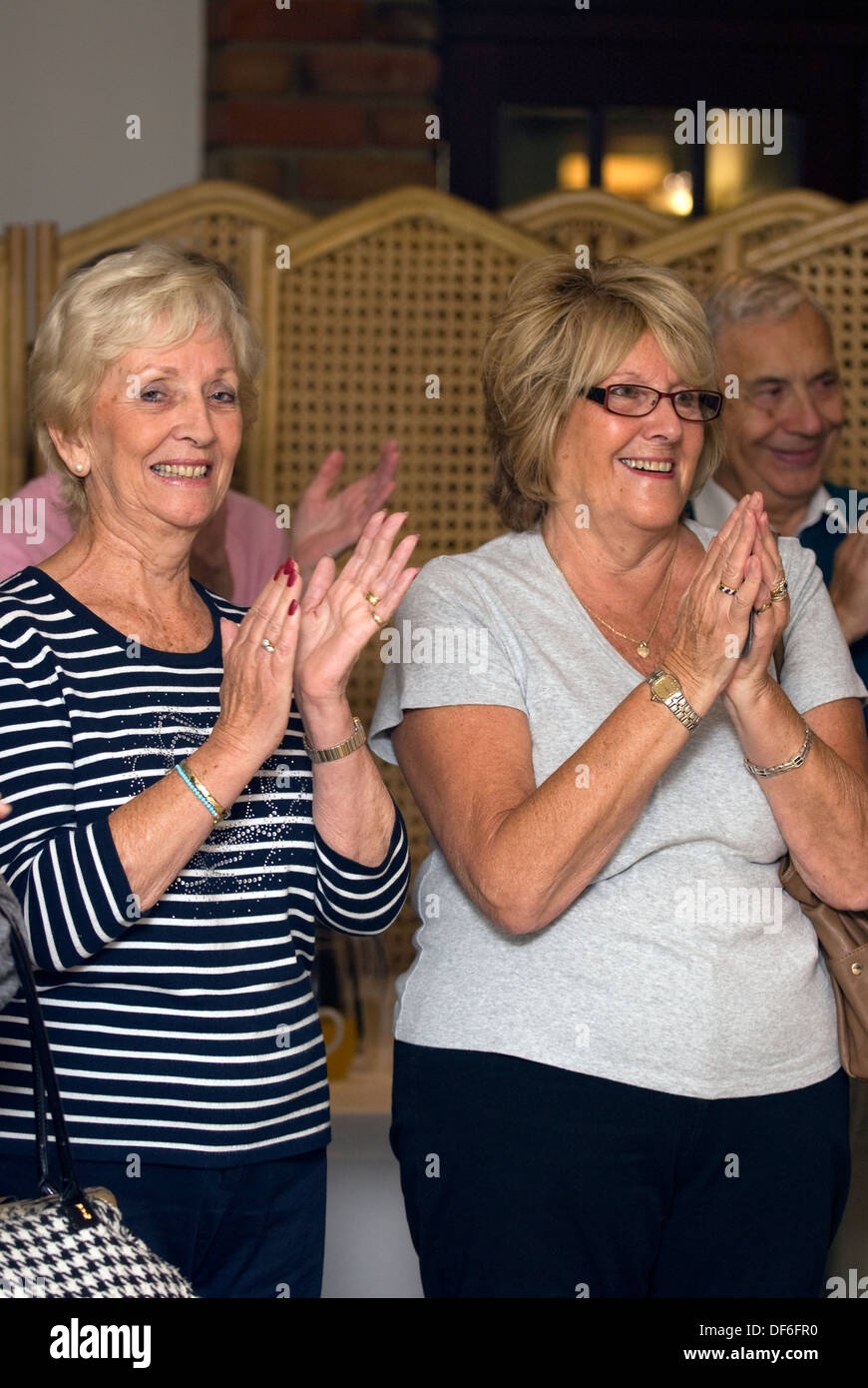 Elderly women showing their appreciation for the entertainment (choir) at a Macmillan Cancer Support Coffee Morning, Surrey, UK - Stock Image