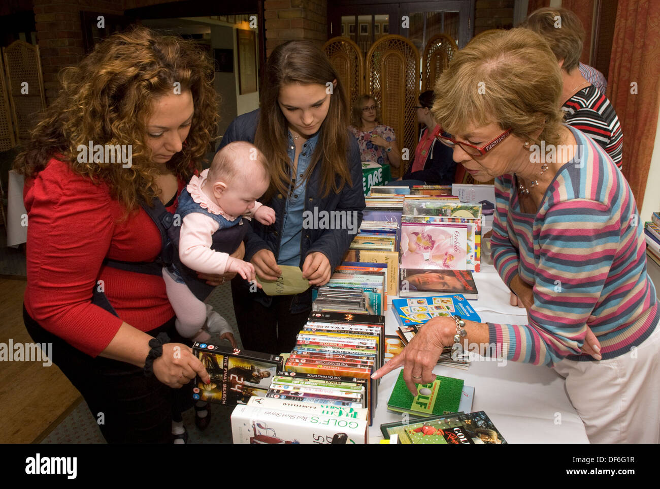 Visitors browsing book and DVD stall at a Macmillan Cancer Support Coffee Morning, Farnham, Surrey, UK. - Stock Image