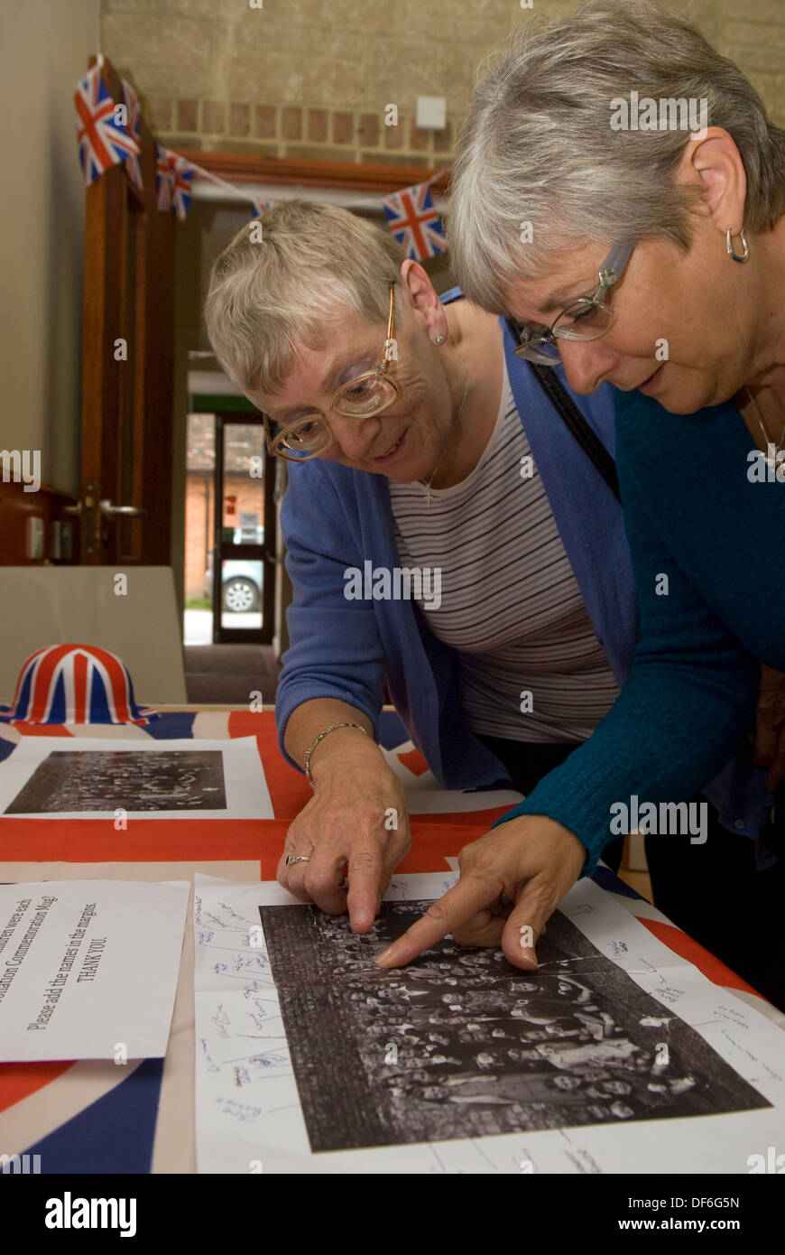 Two elderly women browsing old photographs at a village history open day, Buriton, Hampshire, UK. - Stock Image