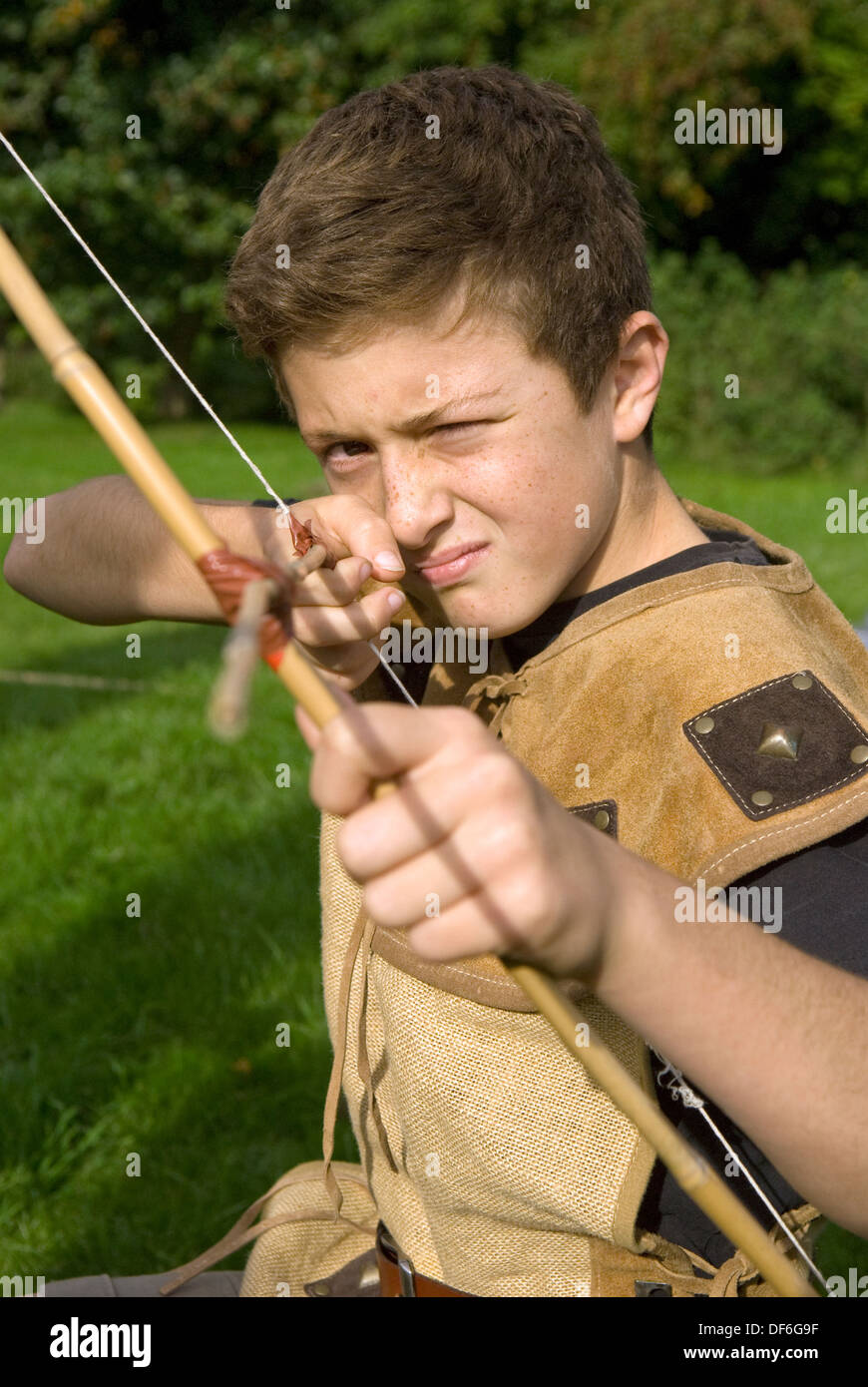 10 year old boy at a local village history open day focussing on the Saxon era learning how to use a bow and arrow - Stock Image