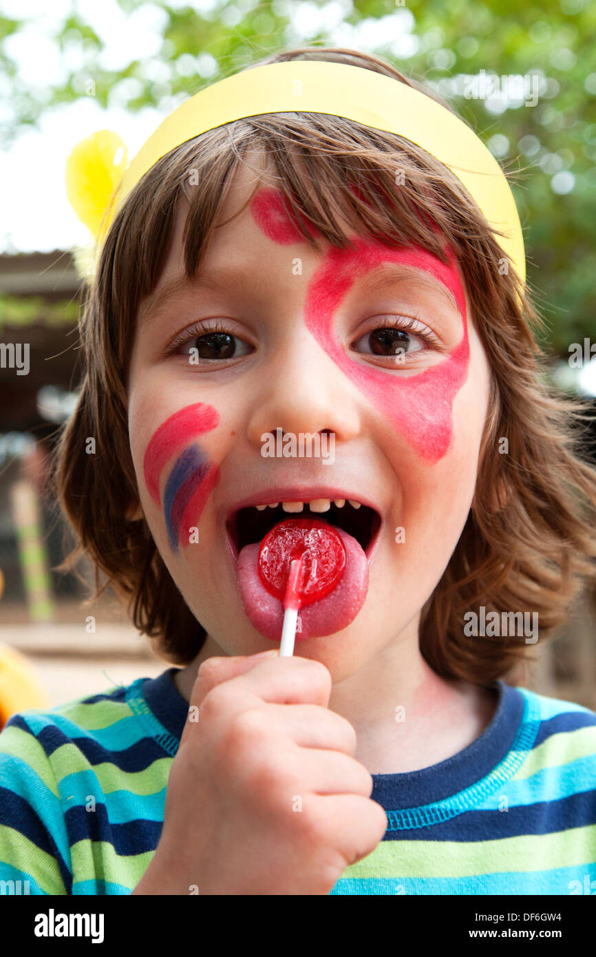 Four year old boy with face paint licking lollipop, Spain. - Stock Image