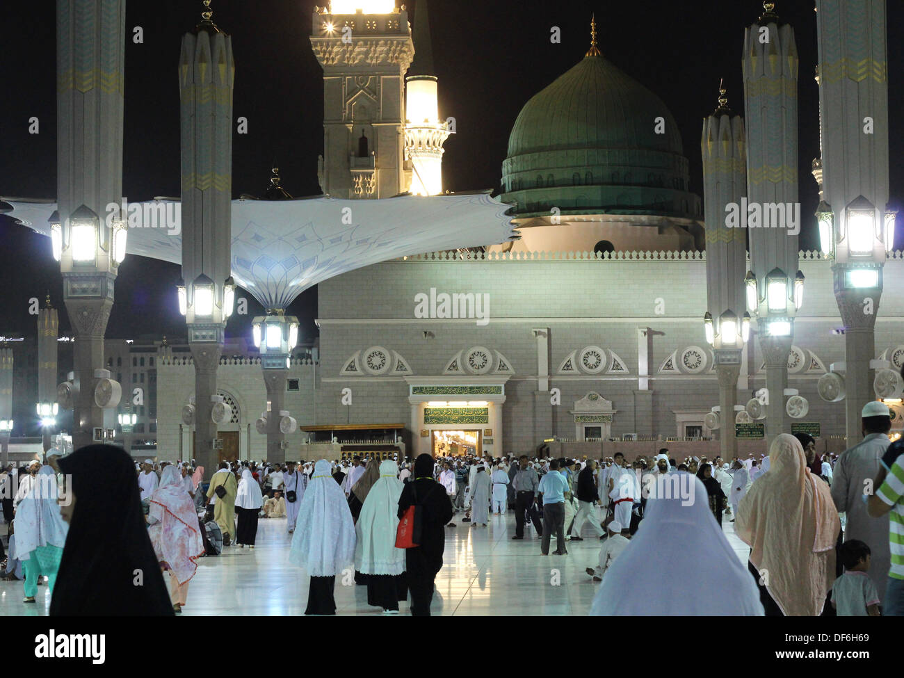 MEDINA, KINGDOM OF SAUDI ARABIA (KSA) - JUNE 6: Muslims walk outside Nabawi Mosque after dusk prayer June 6, 2013. - Stock Image