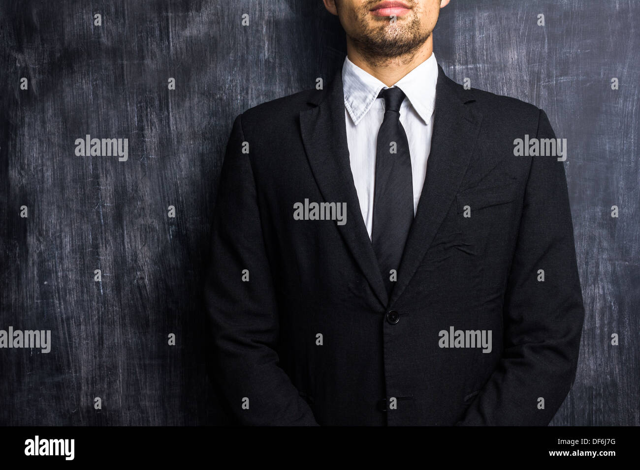 Young businessman standing in front of blackboard - Stock Image