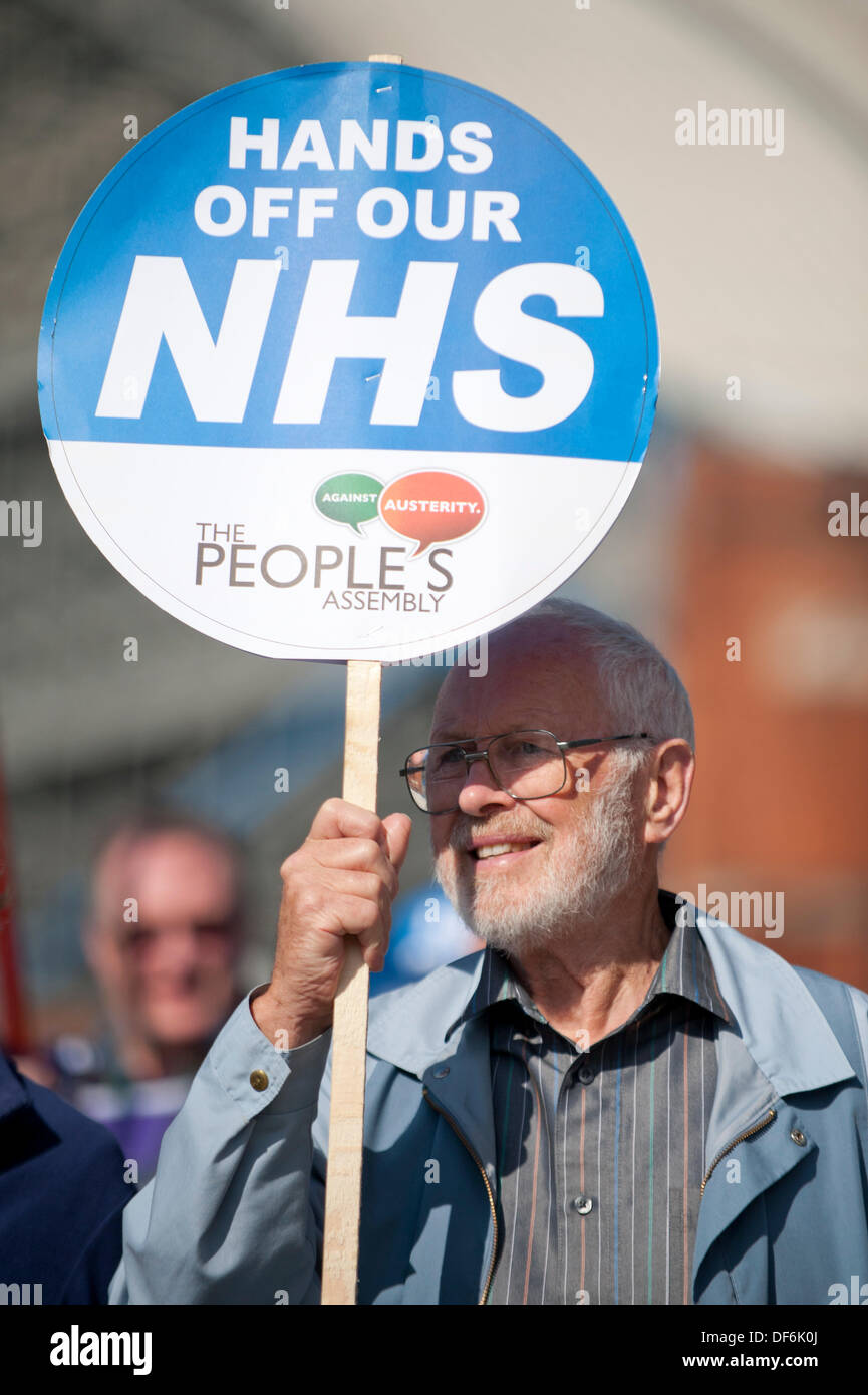 Manchester, UK. 29th Sept 2013. A man in his fifties or sixties holding aloft a sign reading 'Hands off our NHS' during a North West TUC organised march and rally intending to defend National Health Service (NHS) jobs and services from cuts and privatisation. The march coincides with the Conservative Party Conference 2013 being held in the city. Credit:  Russell Hart/Alamy Live News (Editorial use only). - Stock Image