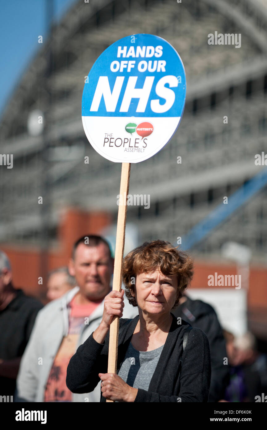 Manchester, UK. 29th Sept 2013. A woman in her fifties holding aloft a sign reading 'Hands off our NHS' - Stock Image