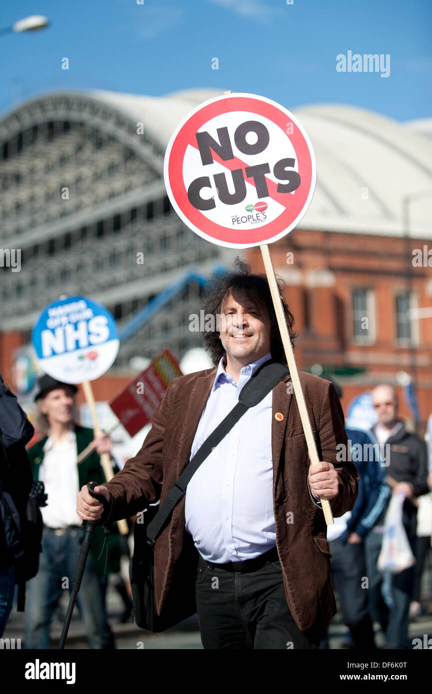 Manchester, UK. 29th Sept 2013. A man in his forties holding aloft a sign reading 'no cuts' during a North - Stock Image