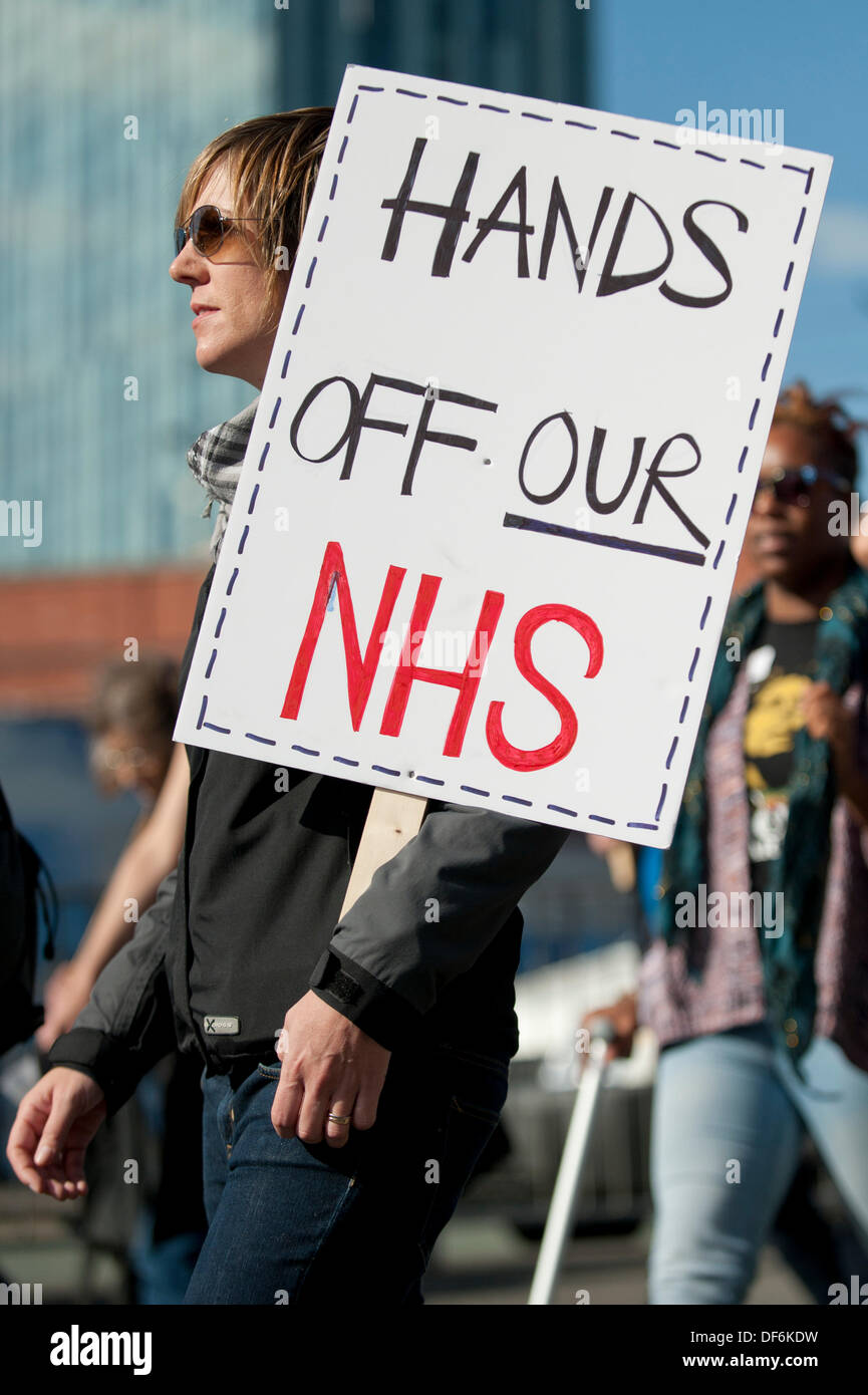 Manchester, UK. 29th Sept 2013. A protestor holding a sign reading 'Hands off our NHS' during a North West TUC organised march and rally intending to defend National Health Service (NHS) jobs and services from cuts and privatisation. The march coincides with the Conservative Party Conference 2013 being held in the city. Credit:  Russell Hart/Alamy Live News. - Stock Image