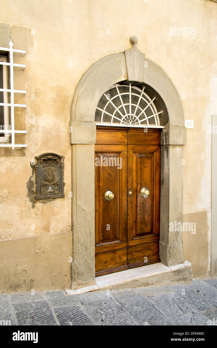 Large wooden doors with brass door knobs and an ornate letter box ...
