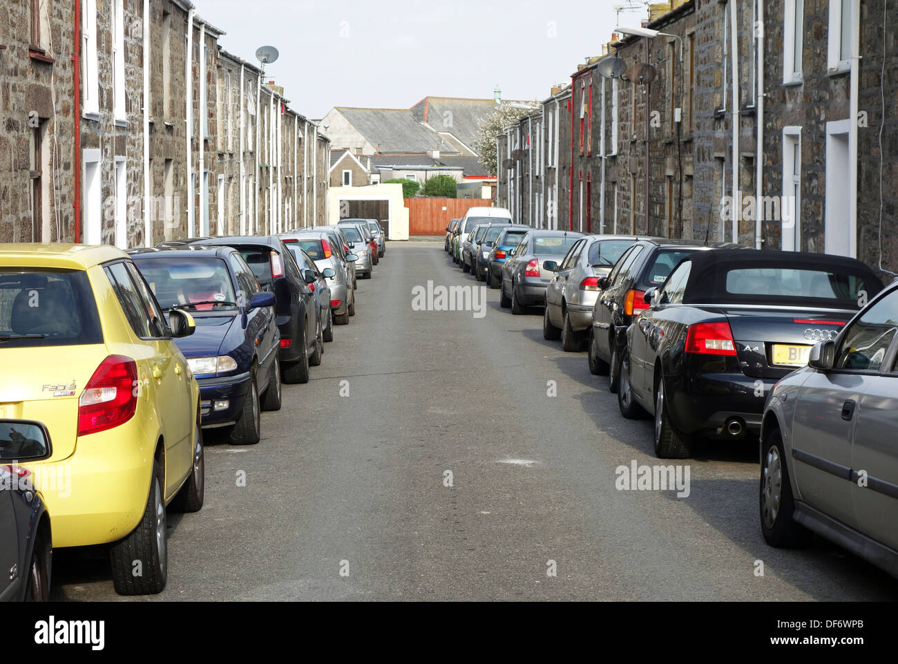 Cars double parked in a narrow street - Stock Image