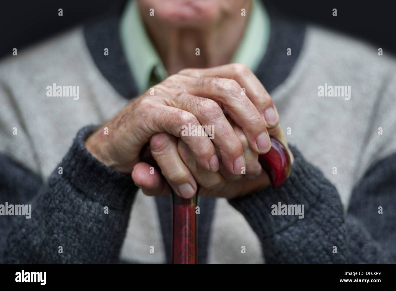 An elderly old age pensioner sits with his hands on a walking stick in a care home. - Stock Image