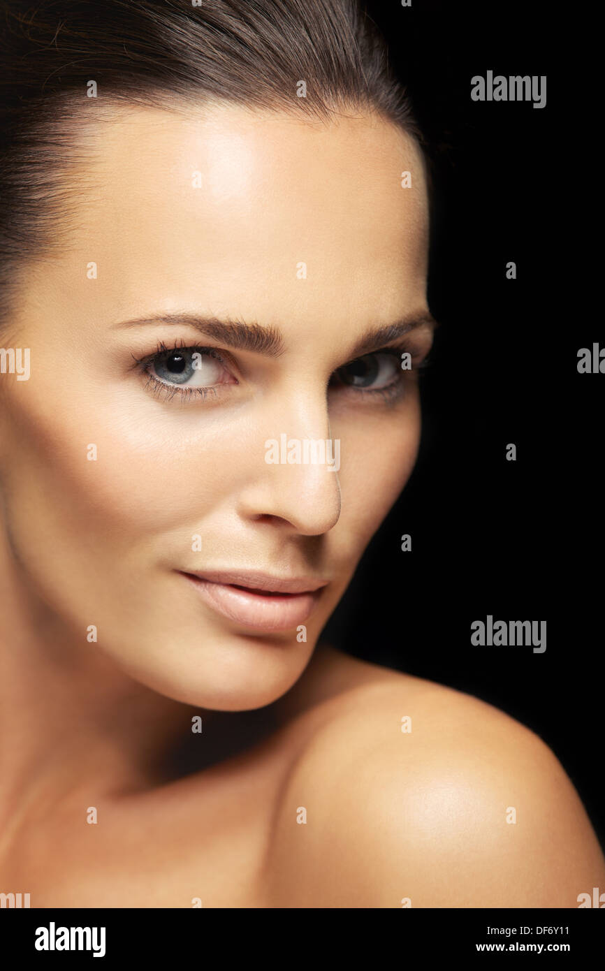 Close-up portrait of a attractive young female with flawless skin looking at camera. Pretty woman with clean and glowing skin - Stock Image