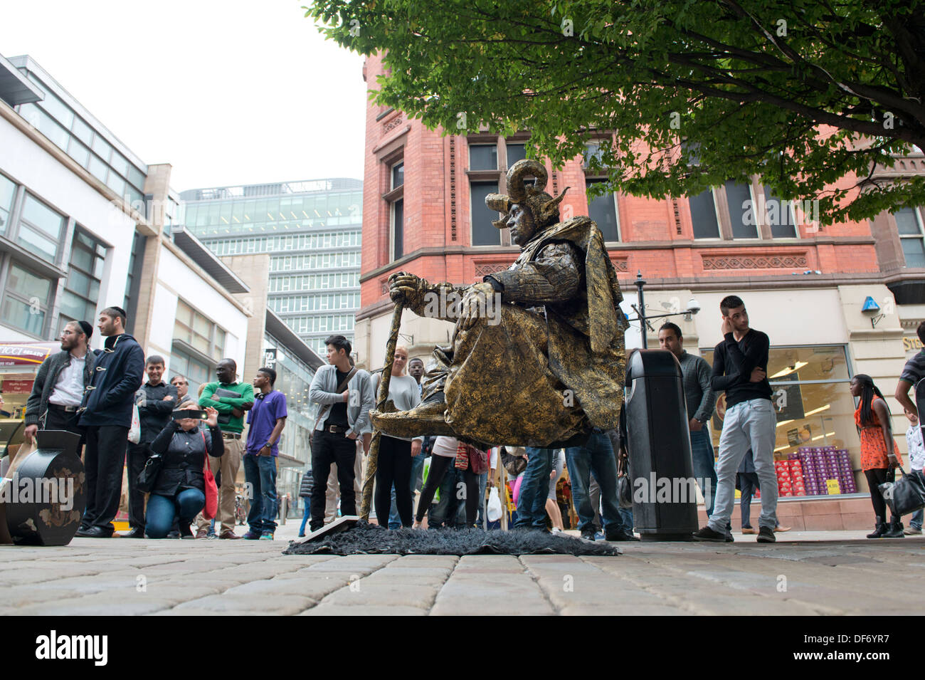 A levitating street artist performs on Market Street in Manchester city centre, watched by passers by. Stock Photo
