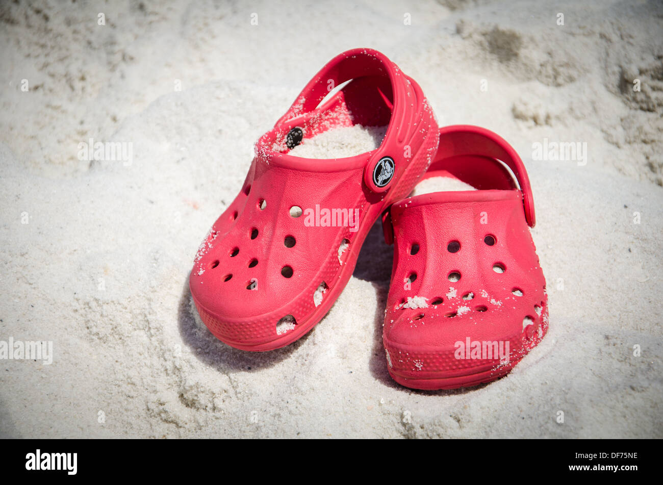 70eca01d9 Pair of Crocs shoes covered in sand on the beach - Stock Image