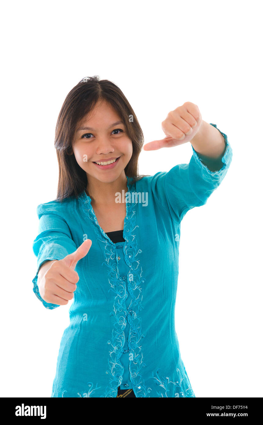 Cute young muslim girl giving a thumb up sign over white background focus on thumb