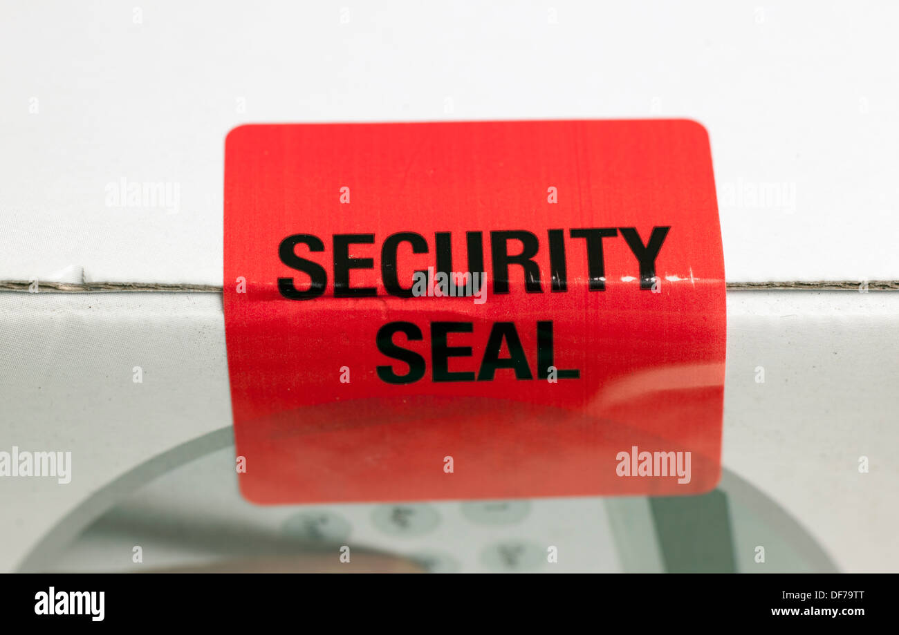 Security seal sealing the side of a cardboard box - Stock Image