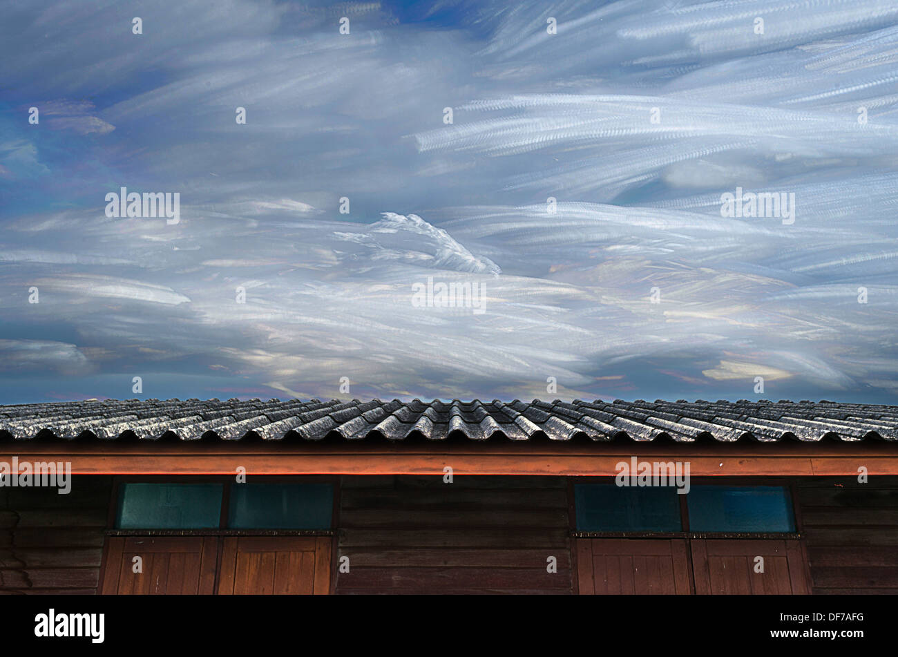 The Moving of Freezing Cloud in Blue Sky Over Roof of Wooden House. - Stock Image