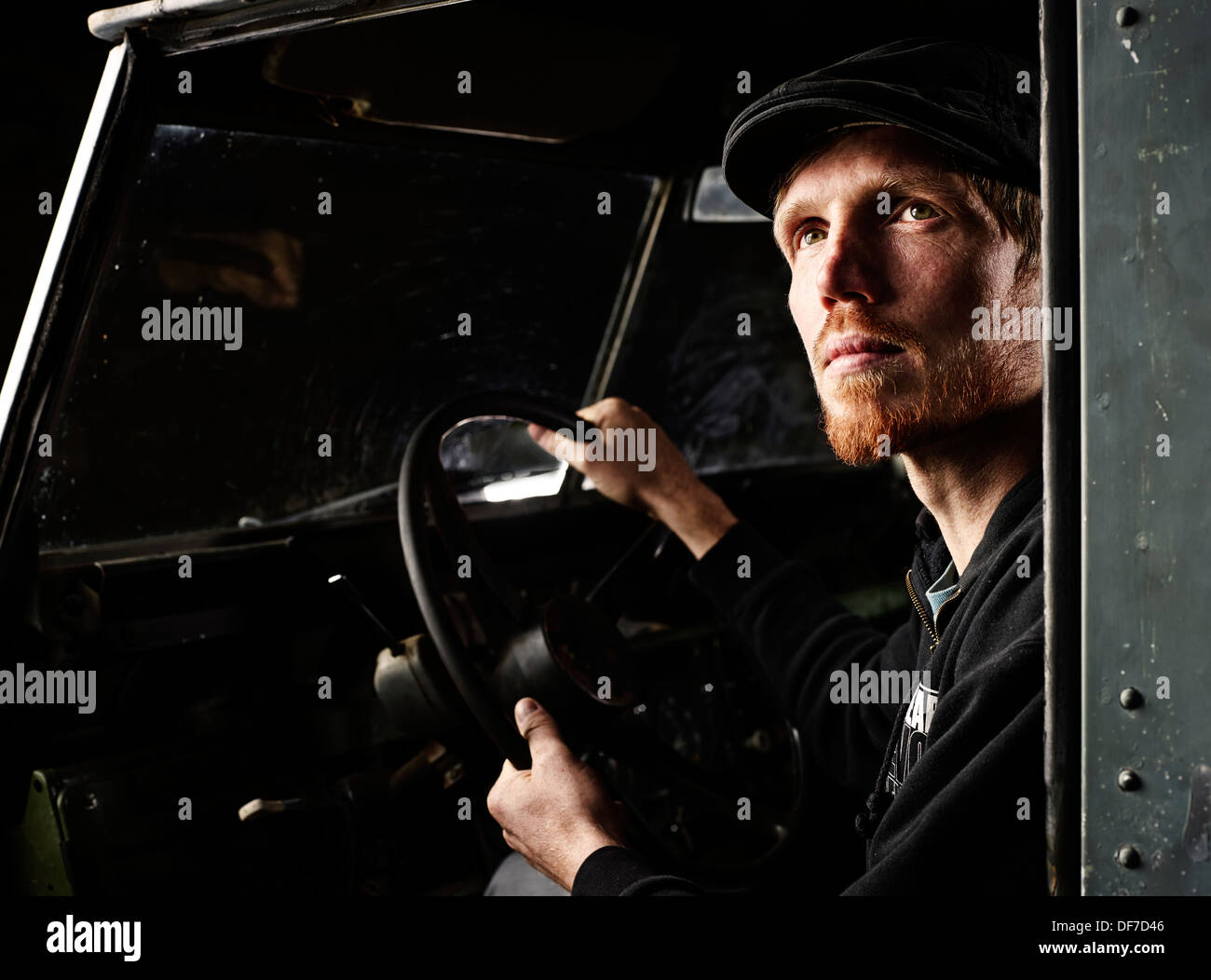 Man with a hat sitting in the driver's seat of an old car, looking up, Inneralpbach, Tyrol, Austria - Stock Image