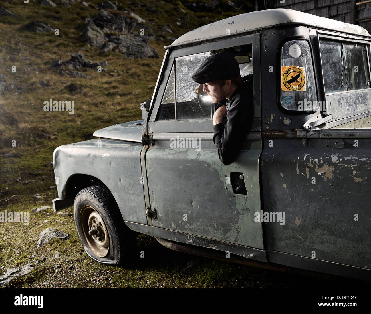 Man with a hat sitting in the driver's seat of an old car noticing a flat front left tyre, Inneralpbach, Tyrol, Austria - Stock Image