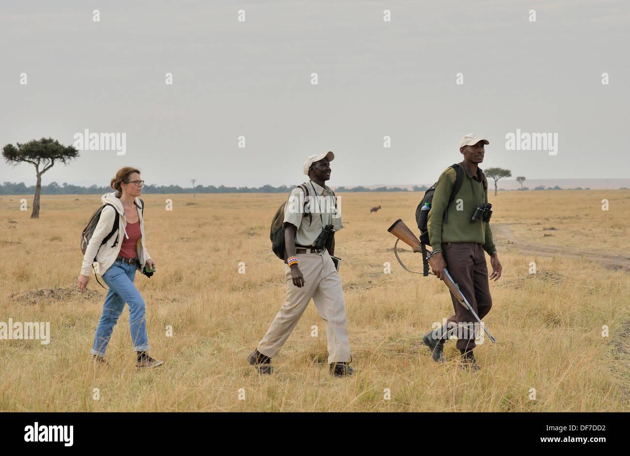 Tourist with armed guard and guide on a walking safari, Massai Mara, Serengeti, Rift Valley province, Kenya - Stock Image