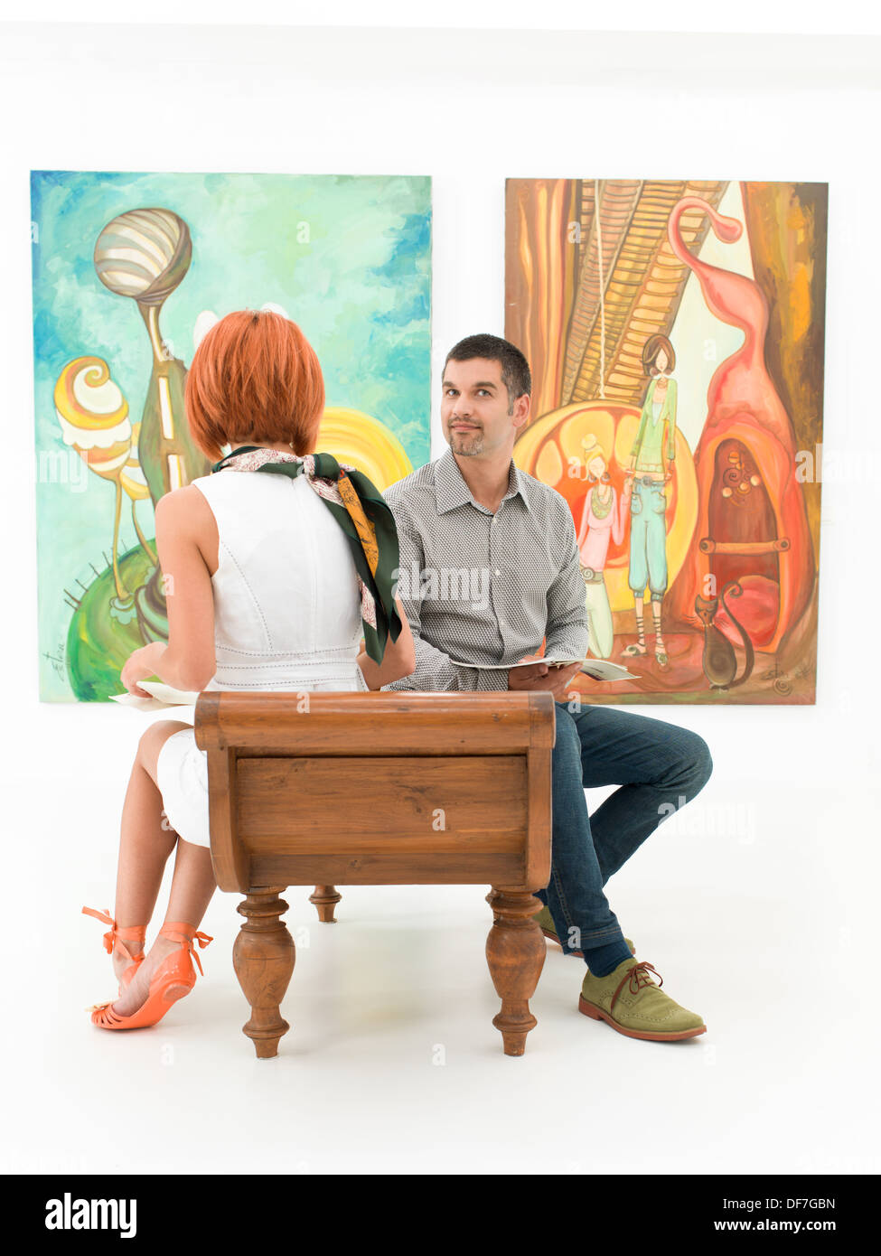 two young caucasian people sitting on a bench contemplating colorful contemporary paintings - Stock Image